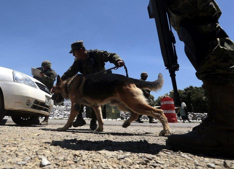 Mexican soldiers inspect a vehicle at a checkpoint on August 2, 2013