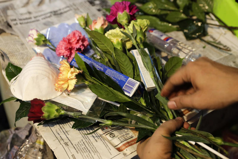 "A man arranges a Valentines flower arrangement which they called ""anti-nCoV bouquet"" in Alabang, metropolitan Manila, Philippines Thursday, Feb. 13, 2020. Shop owner Mary Jane Villegas said she placed protective face masks, alcohol, soap, toothpaste and gloves in her bouquet to remind people that flowers are not the only things you can give during Valentines but also protection against the COVID-19. The ""anti-nCoV"" bouquet is sold for P1,300, or U.S.$26. (AP Photo/Aaron Favila)"