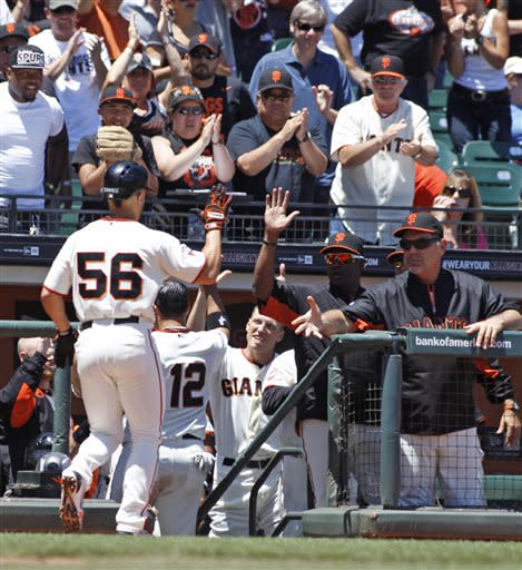 San Francisco Giants' Andres Torres (56) and Guillermo Quiroz (12) are greeted at the dugout during the third inning of a baseball game against the Los Angeles Dodgers in San Francisco, Sunday, July 7, 2013. Quiroz scored on a Torres sacrifice fly. (AP Photo/George Nikitin)