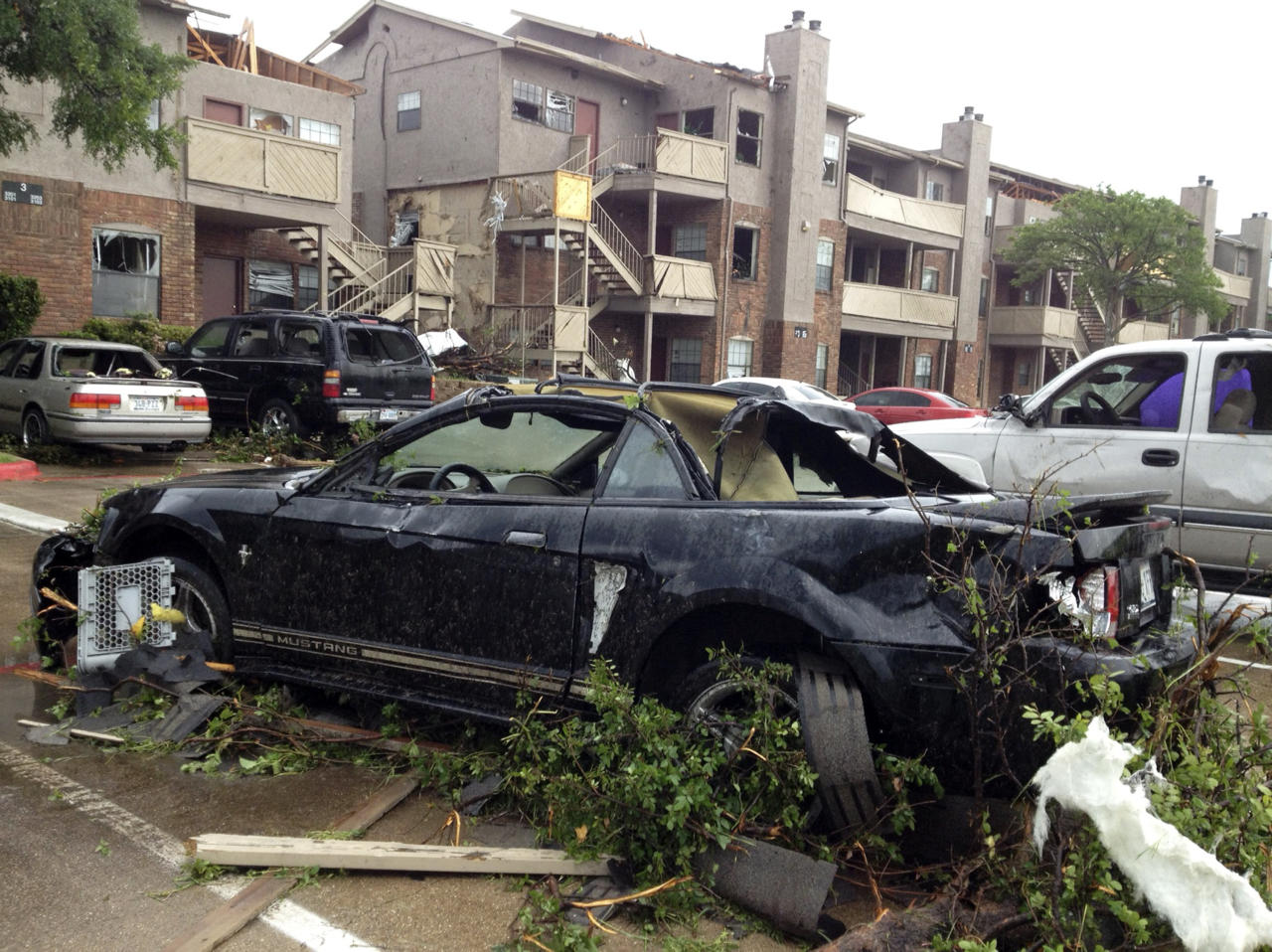 Cars and property at Portofino Apartments at Pleasant Run in Lancaster, Texas are damaged after a storm passed through the area on Tuesday, April 3, 2012. Tornadoes tore through the Dallas area Tuesday, peeling roofs off homes, tossing big-rig trucks into the air and leaving flattened tractor trailers strewn along highways and parking lots. (AP Photo/The Fort Worth Star-Telegram, Ron Ennis) MAGS OUT