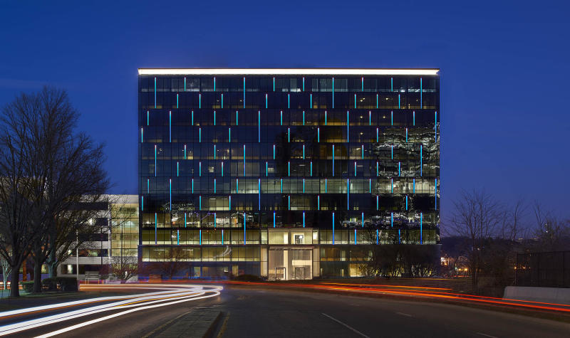 Glass building at dusk with long-exposure streaking headlights.