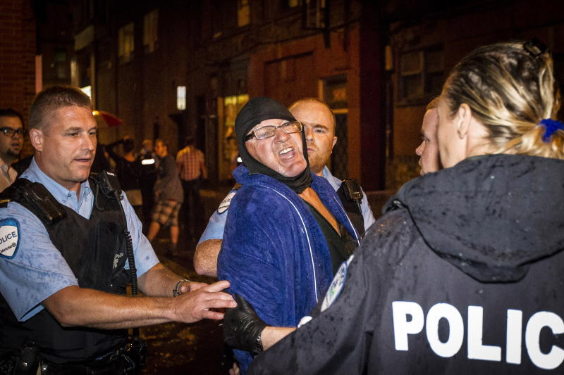 A man is arrested by police outside the Parti Quebecois victory rally in Montreal on Wednesday, Sept. 5, 2012. A masked gunman wearing a blue bathrobe opened fire during a midnight victory rally for Quebec's new premier, killing one person and wounding another. The new premier, Pauline Marois of the separatist Parti Quebecois, was whisked off the stage by guards while giving her speech and uninjured. It was not clear if the gunman was trying to shoot Marois, whose party favors separation for the French-speaking province from Canada. Police identified the gunman only as a 62-year-old man, and were still questioning him Wednesday morning. (AP Photo/Montreal La Presse via The Canadian Press, Olivier Pontbriand)