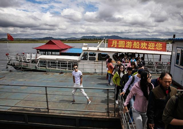 <p>Chinese tourists disembark from a boat on the Yalu river near the border city of Dandong, Liaoning province, northern China across from the city of Sinuiju, North Korea on May 23, 2017 in Dandong, China. (Photo: Kevin Frayer/Getty Images) </p>