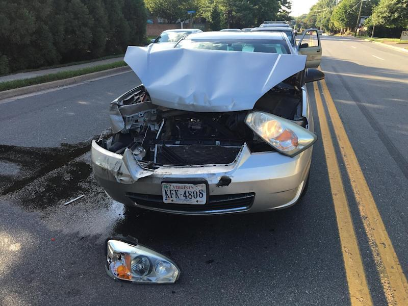 In this photo taken July 14, 2016, a car involved in an accident sits in the road McLean, Va. The Consumer Federation of America says it found premium hikes in some cases reaching $400. It looked at premium quotes in 10 cities from five of the nation's largest auto insurers and found that Progressive aggressively used a not-at-fault penalty, surcharging drivers in eight of the ten cities.  (AP Photo/Jennifer C. Kerr)