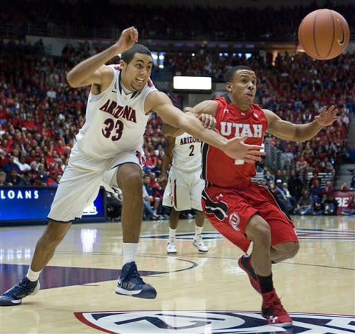 Arizona's Grant Jarrett (33) and Utah's Glen Dean (1) battle for a loose ball during the second half of an NCAA college basketball game at McKale Center in Tucson, Ariz., Saturday, Jan. 5, 2013. Arizona won 60 - 57. (AP Photo/Wily Low)