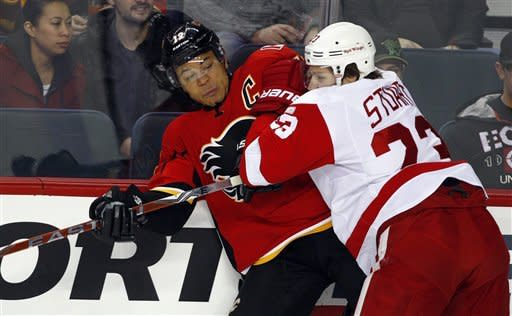 Detroit Red Wings' Brad Stuart, right, checks Calgary Flames' Jarome Iginla during the first period of an NHL hockey game in Calgary, Alberta, Thursday, Dec. 22, 2011. (AP Photo/The Canadian Press, Jeff McIntosh)