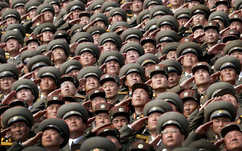 North Korean soldiers salute while the national anthem is played during a military parade on Saturday, April 15, 2017, in Pyongyang, North Korea to celebrate the 105th birth anniversary of Kim Il Sung, the country's late founder and grandfather of current ruler Kim Jong Un. - Credit: Wong Maye-E/AP