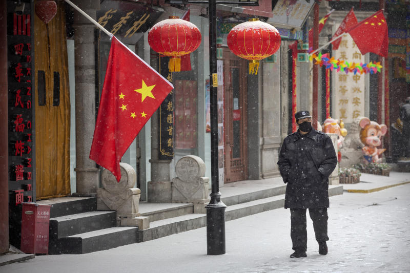 A security guard wears a face mask as he walks along a pedestrian shopping street during a snowfall in Beijing, Wednesday, Feb. 5, 2020. Deaths from a new virus rose to 490 in mainland China on Wednesday while new cases on a Japanese cruise ship, in Hong Kong and in other places showed the increasing spread of the outbreak and renewed attention toward containing it. (AP Photo/Mark Schiefelbein)