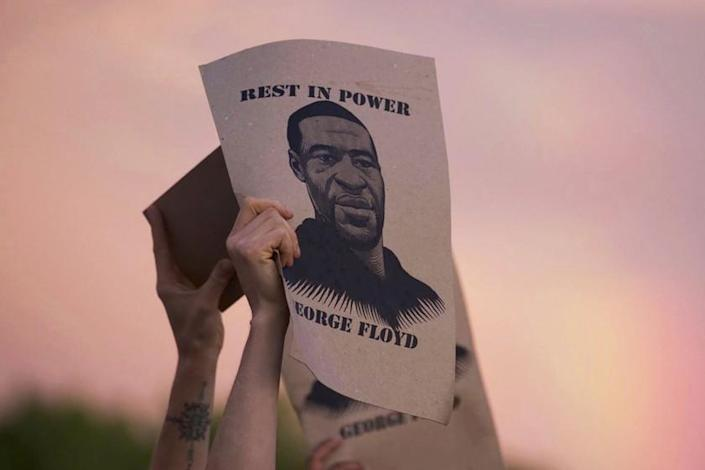 """A sign featuring an image of George Floyd is displayed during a protest in Minneapolis. <span class=""""copyright"""">(Christine T. Nguyen / Minnesota Public Radio)</span>"""
