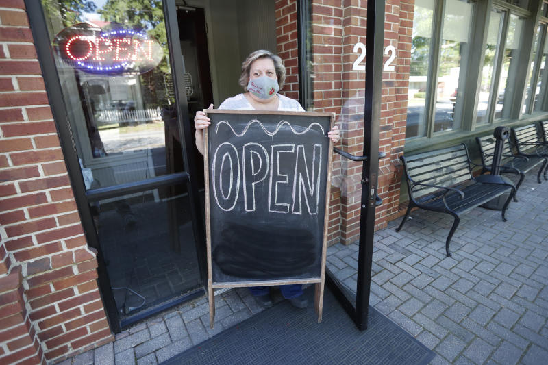 Mary Spoto, general manager of Madison Chop House Grille, places a sign outside the restaurant as she and her staff prepare to shift from take out only to dine-in service Monday, April 27, 2020, in Madison, Ga. (John Bazemore/AP)