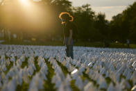 """Zoe Nassimoff, of Argentina, looks at white flags that are part of artist Suzanne Brennan Firstenberg's temporary art installation, """"In America: Remember,"""" in remembrance of Americans who have died of COVID-19, on the National Mall in Washington, Friday, Sept. 17, 2021. Nassimoff's grandparent who lived in Florida died from COVID-19. (AP Photo/Brynn Anderson)"""