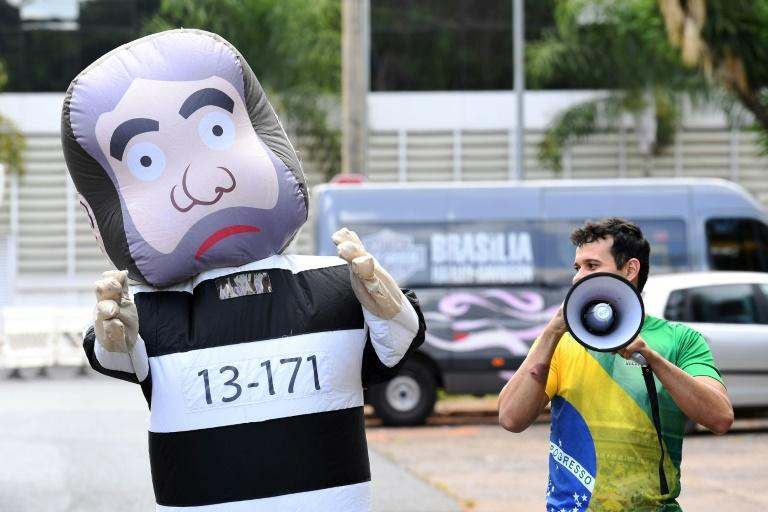 "A man dressed as the doll ""Pixuleco"", representing former Brazilian President Luiz Inacio Lula da Silva, stands outside the federal court building in Brasilia while Lula testifies, on March 14, 2017"