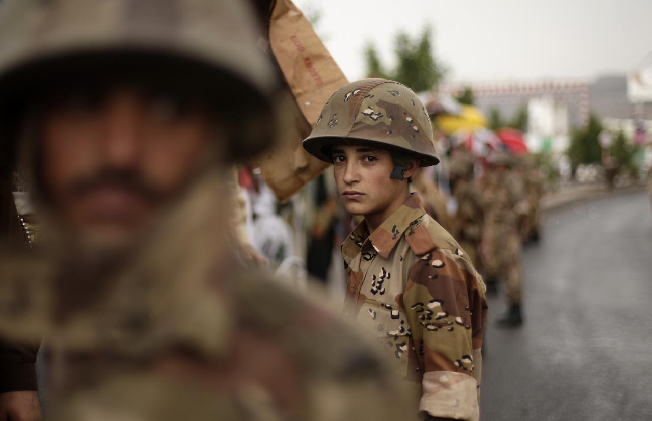 A young Yemeni soldier, center, stands guard as protestors demanding that the relatives of former President Ali Abdullah Saleh be fired from army and police posts demonstrate in Sanaa, Yemen, Friday, July 27, 2012. (AP Photo/Hani Mohammed)