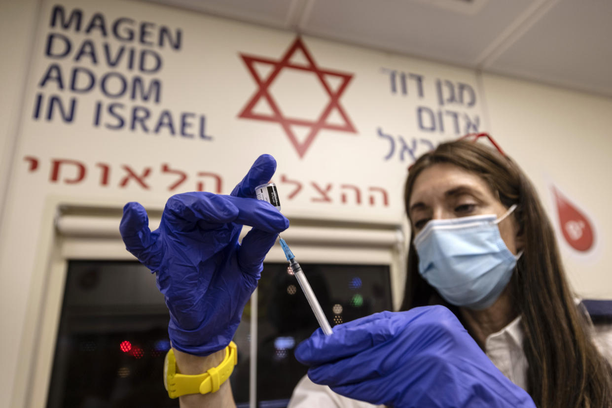A medic from Israel's Magen David Adom emergency service prepares a booster shot of the coronavirus vaccine in Tel Aviv on Aug. 14, 2021.