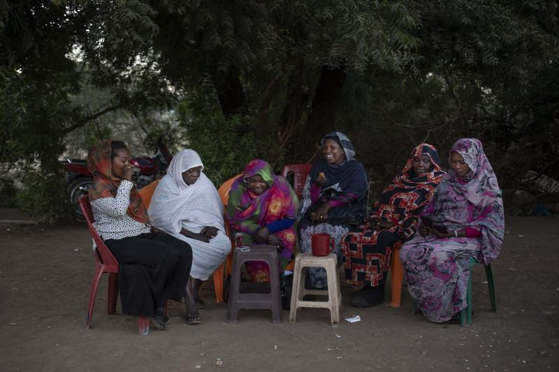 In this Jan. 12, 2020 photo, the head of the Women Tea Vendors' Union, Awadia Coco, second left, sits with other members of the union, which supports women's rights, as they drink tea on a street in Khartoum, Sudan. Many tea vendors were sexually assaulted during the June 3, 2019 crackdown on a protest camp in Khartoum. The Associated Press spoke to six rape victims. They told similar stories of Rapid Support Forces fighters corralling up fleeing protesters, beating them, sexually molesting the women and gang-raping some. (AP Photo/Nariman El-Mofty)