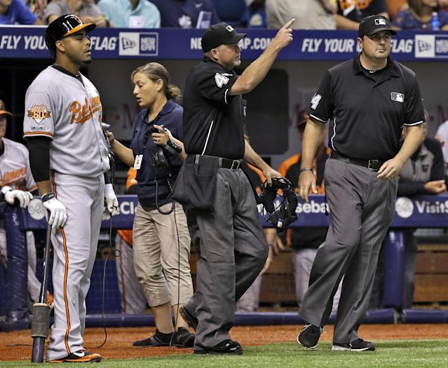 Home plate umpire Ron Kulpa, center, signals that a ball hit by Baltimore Orioles' Chris Davis is a grand slam off Tampa Bay Rays starting pitcher Erik Bedard during the third inning of a baseball game Tuesday, June 17, 2014, in St. Petersburg, Fla. Looking on is Orioles' Nelson Cruz, left, and third base umpire Lance Barrett, right. (AP Photo/Chris O'Meara)
