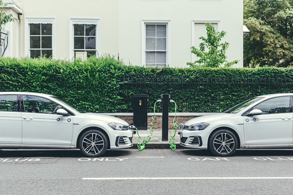 London/UK-30/07/18: two white Volkswagen Golf GTE cars charging at a charging point on a street in London. The Golf GTE is a plug-in hybrid version of the Golf hatchback