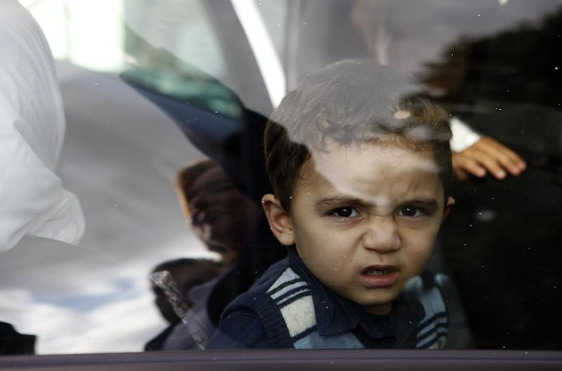 """Bushr Al Tawashi is seen through a window car with Cypriot lawyer Stella Constantinou reflected, outside of a private Sigma TV station, in Nicosia, Cyprus, Friday, Oct. 26, 2012. A 2-year-old Syrian boy who was believed dead after his family inadvertently left him behind as they fled shelling in Damascus last summer has been reunited with his parents in Cyprus, a lawyer said. """"You can imagine how they felt when they were told their son was alive after bearing all this guilt thinking that he was dead,"""" lawyer Stella Constantinou told The Associated Press. (AP Photo/Petros Karadjias)"""