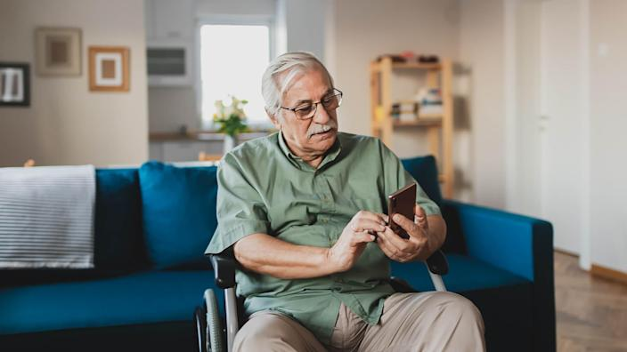 Handicapped senior person sitting in a wheelchair and using a smart phone at home in the living room.