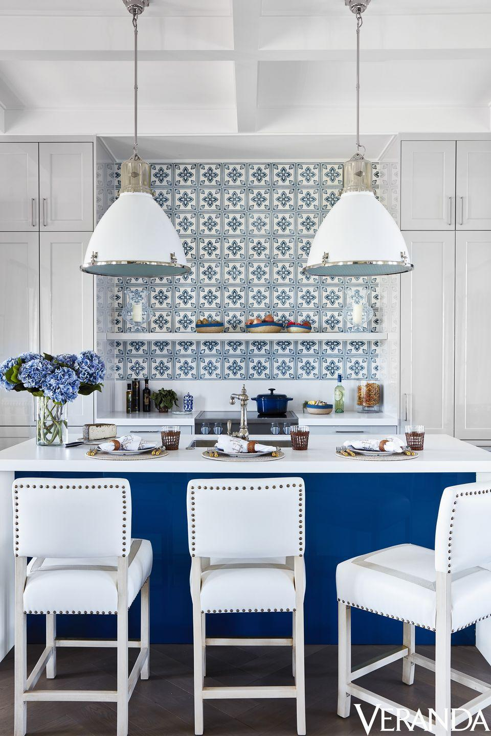 """<p>At this Windsor, Florida, cottage, designer Alessandra Branca packed a powerful style punch with the blue and white <a href=""""http://www.casablancatile.com/"""" rel=""""nofollow noopener"""" target=""""_blank"""" data-ylk=""""slk:Casa Branca"""" class=""""link rapid-noclick-resp"""">Casa Branca</a> tile backsplash, which stands in colorful contrast to a sleek, lacquered <a href=""""https://www.siematic.com/en/"""" rel=""""nofollow noopener"""" target=""""_blank"""" data-ylk=""""slk:SieMatic"""" class=""""link rapid-noclick-resp"""">SieMatic</a> island. The <a href=""""http://www.palecek.com/"""" rel=""""nofollow noopener"""" target=""""_blank"""" data-ylk=""""slk:Palecek"""" class=""""link rapid-noclick-resp"""">Palecek</a> stools are covered in a <a href=""""https://www.kravet.com/"""" rel=""""nofollow noopener"""" target=""""_blank"""" data-ylk=""""slk:Kravet"""" class=""""link rapid-noclick-resp"""">Kravet</a> fabric with <a href=""""https://samuelandsons.com/"""" rel=""""nofollow noopener"""" target=""""_blank"""" data-ylk=""""slk:Samuel & Sons"""" class=""""link rapid-noclick-resp"""">Samuel & Sons</a> trim. Fittings, <a href=""""https://go.redirectingat.com/?id=74968X1525088&xs=1&url=http%3A%2F%2Fwww.kohler.com%2Fcorporate%2Findex.html&sref=https%3A%2F%2Fwww.veranda.com%2Fdecorating-ideas%2Fa19833976%2Falessandra-branca-windsor-florida-village-suites%2F&xcust=%5Butm_source%7C%5Butm_campaign%7C%5Butm_medium%7C%5Bgclid%7C%5Bmsclkid%7C%5Bfbclid%7C%5Brefdomain%7Cgoogle.com%5Bcontent_id%7Cbe0949c9-1e96-4ab0-a1a4-e2ed88e68ef4%5Bcontent_product_id%7C%5Bproduct_retailer_id%7C"""" rel=""""nofollow noopener"""" target=""""_blank"""" data-ylk=""""slk:Kohler"""" class=""""link rapid-noclick-resp"""">Kohler</a>. Pendants, <a href=""""https://www.circalighting.com/"""" rel=""""nofollow noopener"""" target=""""_blank"""" data-ylk=""""slk:Circa Lighting"""" class=""""link rapid-noclick-resp"""">Circa Lighting</a>.</p>"""