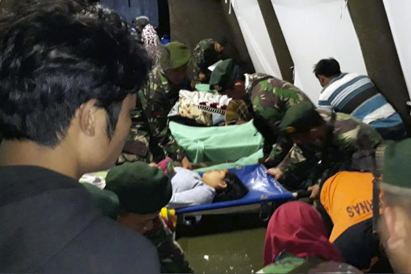 Indonesian soldiers tend to a woman injured after a magnitude 7.0 earthquake struck Lombok