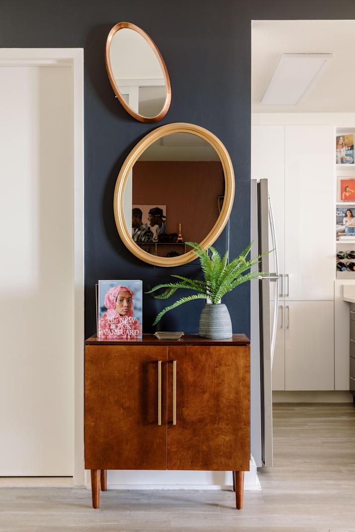 "One of Taylor's favorite elements of her space is the variety of mirrors found in the apartment. They were also ""important in finding balance with darker colors in a smaller space,"" Jannah and Kiyanna share."