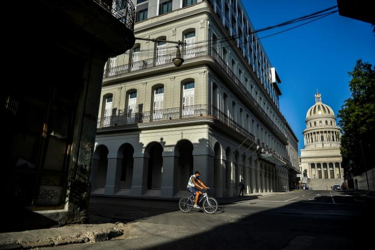 A man rides on his bicycle along an empty street in Havana on May 19, 2020, amid the new coronavirus pandemic. The pandemic has increased pressure on the country which was already suffering food and fuel shortages