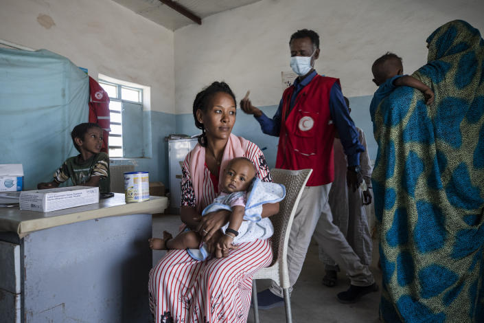 Surgeon and doctor-turned-refugee, Dr. Tewodros Tefera, prepares to preform a medical checkup on an infant, inside the Sudanese Red Crescent clinic in Hamdayet, eastern Sudan, near the border with Ethiopia, on March 22, 2021. (AP Photo/Nariman El-Mofty)