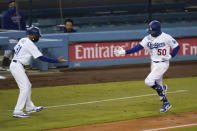 Los Angeles Dodgers' Mookie Betts, right, keeps distance as he celebrates his second home run of a baseball game with third base coach Dino Ebel during the fourth inning against the San Diego Padres, Thursday, Aug. 13, 2020, in Los Angeles. (AP Photo/Jae C. Hong)