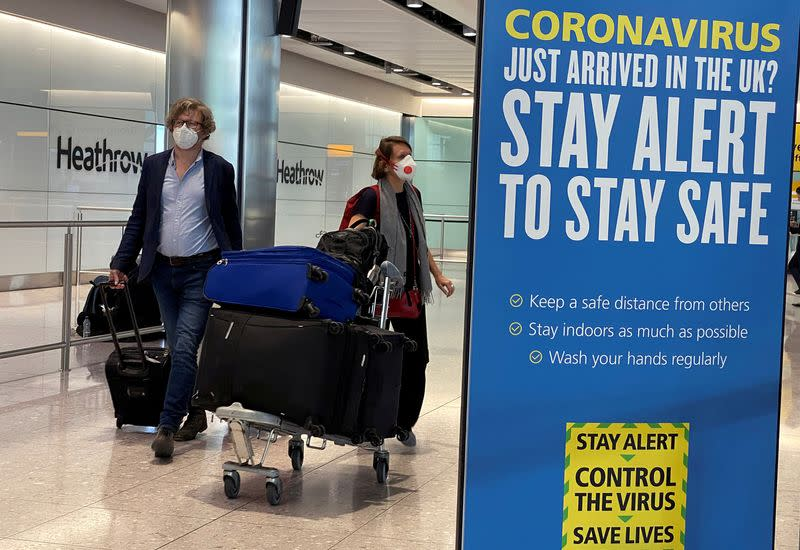 FILE PHOTO: Passengers arrive at Heathrow Airport, as Britain launches its 14-day quarantine for international arrivals, following the outbreak of the coronavirus disease (COVID-19), London, Britain