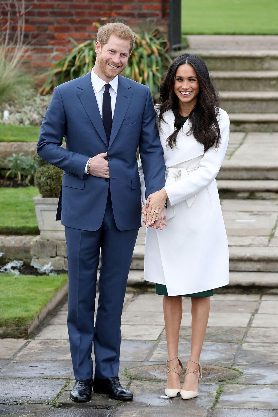 <p>Meghan and Harry hold hands during an official photocall to announce their engagement at the Sunken Gardens at Kensington Palace.</p>