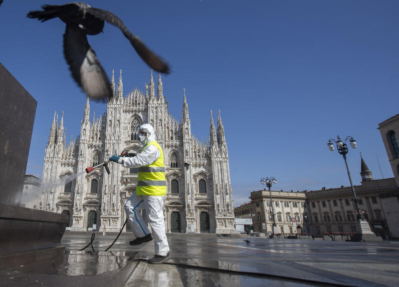 A worker sprays disinfectant to sanitize Duomo square in downtown Milan, Italy, Tuesday, March 31, 2020. The new coronavirus causes mild or moderate symptoms for most people, but for some, especially older adults and people with existing health problems, it can cause more severe illness or death. (AP Photo/Luca Bruno)