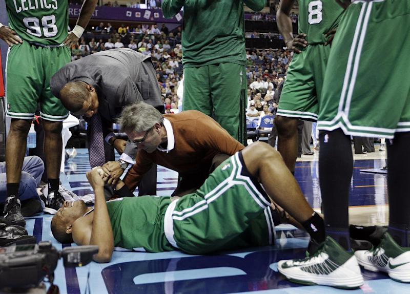 Boston Celtics head coach Doc Rivers, top left, holds the hand of Leandro Barbosa, bottom, as a trainer examines him during the second half of an NBA basketball game against the Charlotte Bobcats in Charlotte, N.C., Monday, Feb. 11, 2013. Barbosa left the game. The Bobcats won 94-91. (AP Photo/Chuck Burton)