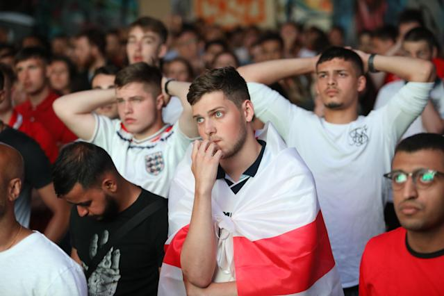 <p>A heartbroken England fan draped in a Three Lions flag reflects the sorrow of the nation. (SWNS) </p>