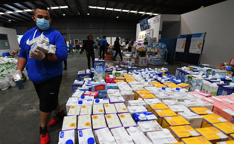 A volunteer helps organise donated food supplies