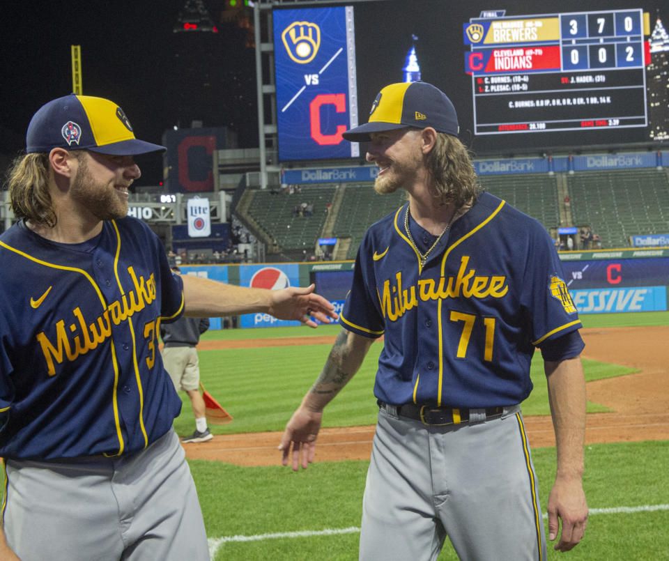 Milwaukee Brewers starter Corbin Burnes, left, and reliever Josh Hader celebrate after pitching a combined no-hitter against the Cleveland Indians in a baseball game in Cleveland, Saturday, Sept. 11, 2021. (AP Photo/Phil Long)