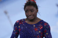 Simone Biles, of the United States, reacts after performing on the uneven bars during the women's artistic gymnastic qualifications at the 2020 Summer Olympics, Sunday, July 25, 2021, in Tokyo. (AP Photo/Gregory Bull)