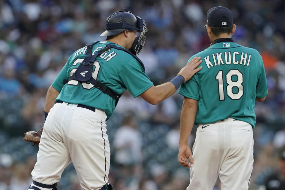 Seattle Mariners catcher Cal Raleigh, left, talks with starting pitcher Yusei Kikuchi during the fourth inning of the team's baseball game against the Oakland Athletics, Friday, July 23, 2021, in Seattle. (AP Photo/Ted S. Warren)