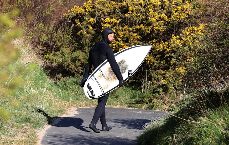 Only those within walking distance of the beach are allowed to surf, according to government guidelines (Owen Humphreys/PA)