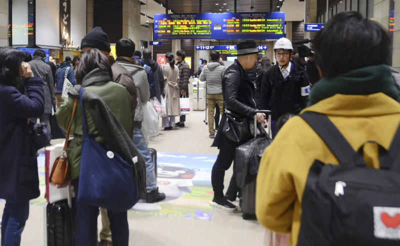 Passengers check the timetable after an earthquake stopped and delayed some train services at JR Kumamoto station in Kumamoto, western Japan, Thursday, Jan. 3, 2019. An earthquake shook southwestern Japan on Thursday, but there were no immediate reports of damage and a tsunami watch was lifted within an hour. (Kyodo News via AP)