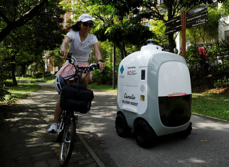 A cyclist passes as Carmello, an autonomous grocery delivery robot, makes its way during a delivery in Singapore
