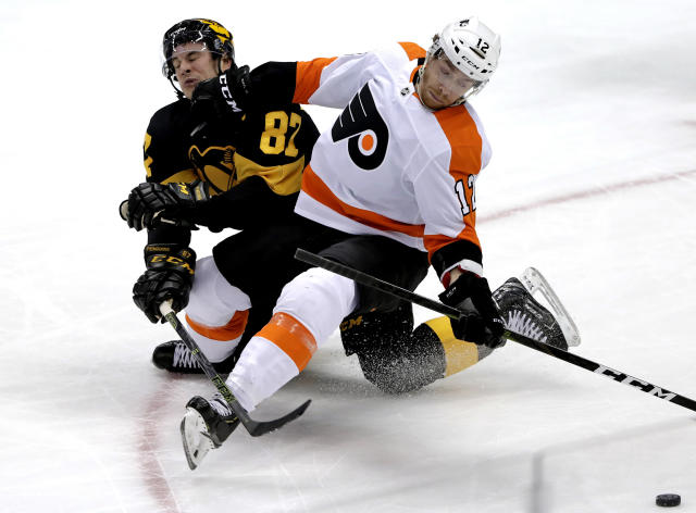 Philadelphia Flyers' Michael Raffl (12) collides with Pittsburgh Penguins' Sidney Crosby (87) during the first period of an NHL hockey game in Pittsburgh, Sunday, March 17, 2019. (AP Photo/Gene J. Puskar)