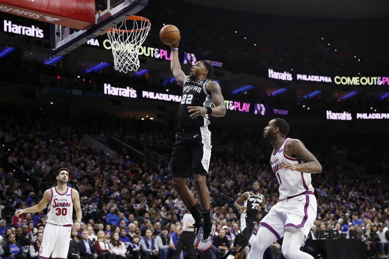 San Antonio Spurs' Rudy Gay (22) goes up for a dunk between Philadelphia 76ers' Furkan Korkmaz (30) and Mike Scott (1) during the second half of an NBA basketball game Friday, Nov. 22, 2019, in Philadelphia. Philadelphia won 115-104. (AP Photo/Matt Slocum)