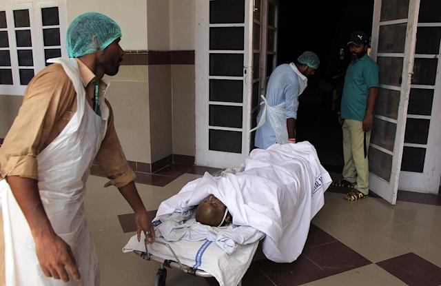 <p>Pakistani hospital staff transport a victim of an oil tanker explosion at a hospital in Multan, Pakistan, Sunday, June 25, 2017. An overturned oil tanker burst into flames in Pakistan on Sunday, killing scores of people who had rushed to the scene of the highway accident to gather leaking fuel, an official said. (AP Photo/Adeel Khan) </p>