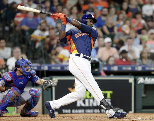 Houston Astros designated hitter Yordan Alvarez connects for an RBI-single in front of Texas Rangers catcher Jeff Mathis, left, during the fifth inning of a baseball game Sunday, July 21, 2019, in Houston. (AP Photo/Michael Wyke)