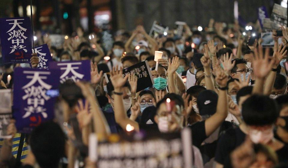 Hong Kong residents hold up their hands at last year's banned Victoria Park vigil, signalling the protest movement's 'five demands, not one less' slogan. Photo: Sam Tsang