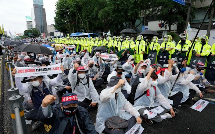 """Workers shout slogans during a rally demanding job security in Seoul, South Korea, Saturday, July 3, 2021. Thousands of workers gathered ignoring the government's call to cancel the assembly feared to affect the fight against COVID-19. The banners read: """"Revision of the labor law."""" (AP Photo/Ahn Young-joon) - AP"""