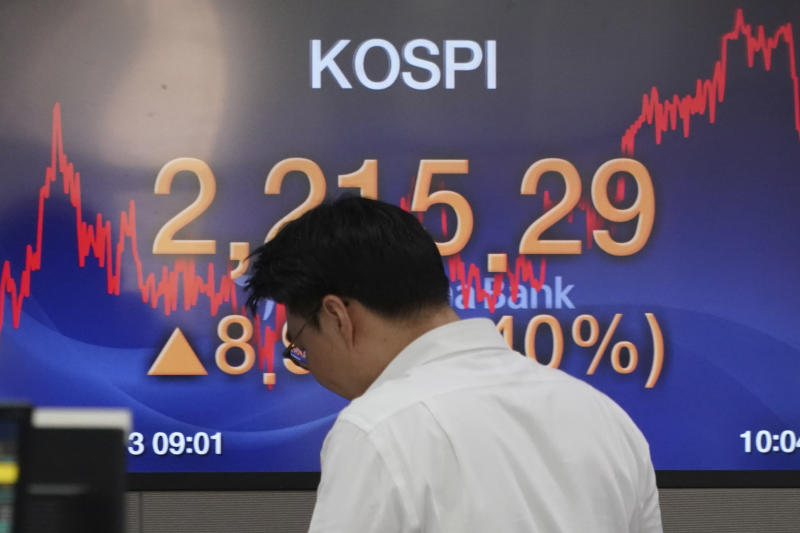 A currency trader walks by the screen showing the Korea Composite Stock Price Index (KOSPI) at the foreign exchange dealing room in Seoul, South Korea, Monday, Jan. 13, 2020. Asian stocks have risen as investors shrug off weaker-than-expected American jobs data and look ahead to the signing of a U.S.-China trade deal. Benchmarks in Shanghai, Hong Kong and Southeast Asia all advanced. (AP Photo/Lee Jin-man)