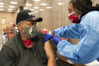 """In this Thursday, Feb. 11, 2021, photo Reginald Henry, 69, of Washington, receives his second dose of the COVID-19 vaccine at a clinic at Howard University, in Washington. """"I felt confident about getting the vaccine,"""" says Henry, who lives in a senior building, """"because God helps those who help themselves."""" (AP Photo/Jacquelyn Martin)"""