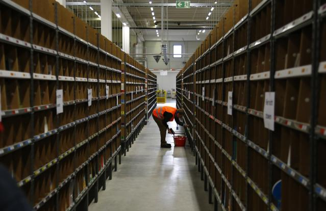 A worker sorts items for delivery from the 70,000 square metre warehouse floor at Amazon's distribution center in Brieselang, near Berlin. (REUTERS/Tobias Schwarz)